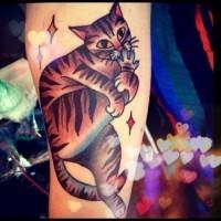 Tatuaggio colorato il gatto che lecca la zampa sua