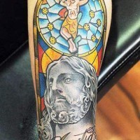 Coloured crucifixion of jesus forearm tattoo