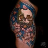Tatuaje cráneo realista con flores de cerezo pintorescas