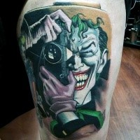 Comic books style colored thigh tattoo of smiling Joker with camera