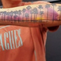 Cool colored beach with palm trees tattoo on arm