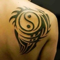 Cool sharp dark black ink Yin Yang special stylized symbol tattoo on man's shoulder blade with tribal elements