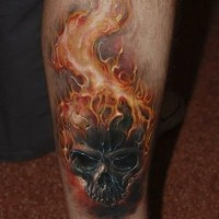 cranio nero brucia in fuoco tatuaggio sulla gamba