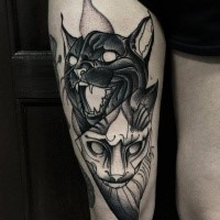 Creepy looking blackwork style thigh tattoo of black and white cats by Michele Zingales