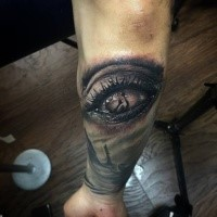 Creepy looking colored arm tattoo of human eye with hands