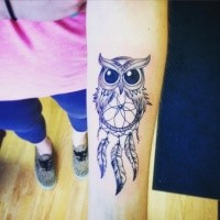 Cute cartoon style black ink forearm tattoo of owl with dream catcher
