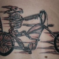 Cute dog skeleton on a bike tattoo