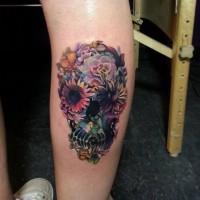 Tatuaggio bellissimo sulla gamba il teschio decorato con i fiori