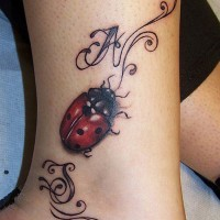 Cute ladybug ankle tattoo with curls