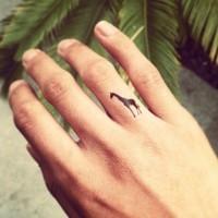 Cute little black ink giraffe tattoo on finger