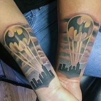 Cute looking colored forearm tattoo of night city with Batman symbol