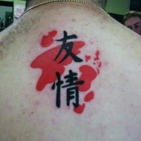 Dark black Asian hieroglyphs with red ink elements tattoo on man's upper back