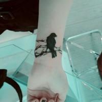 Dark black crow sitting on branch mystical lady's wrist tattoo