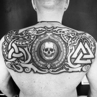 Dark black ink upper back tattoo of human skull with various symbols