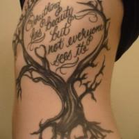 Tatuaje en las costillas, árbol seco y inscripción
