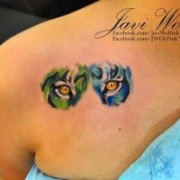 Deep look of tiger's eyes green and blue side colored tattoo on shoulder blade by Javi Wolf