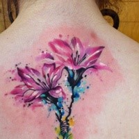 Delicate pink lily flowers tattoo on upper back in watercolor style