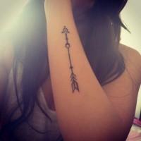 disegno geometrico freccia tatuaggio su braccio di donna