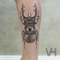 Tatuaggio del braccio dall'aspetto freddo alla moda di un grosso insetto stilizzato con un teschio umano