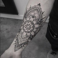Dot work style large forearm tattoo of creative looking floral ornament