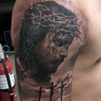 Dramatic religious themed shoulder tattoo of Jesus portrait