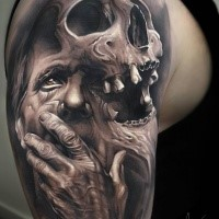 Dramatic very detailed upper arm tattoo of old man with skull