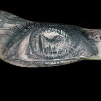 Dramaturgisches im 3D Stil sehr detailliertes menschliches Auge Tattoo am Unterarm mit Sehenswürdigkeiten der Stadt