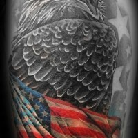 Eagle wrapped in american flag tattoo on arm
