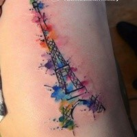 Eiffel Tower with rainbow colored paint drips tattoo on side by Jave Wolf in watercolor style