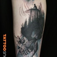 Engraving style black and white forearm tattoo of big skull stylized with forest and moon