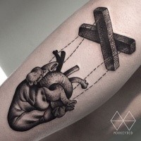 Engraving style black ink arm tattoo of human heart puppet