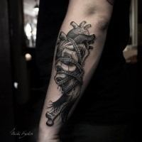Engraving style black ink arm tattoo of human heart with bones and rope