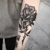 Engraving style black ink forearm tattoo of big rose with human skull