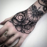 Engraving style black ink wrist tattoo of big rose and ornaments