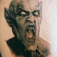 Fantastic designed and painted creepy vampire monster tattoo on leg