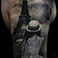 Fantastic looking colorful shoulder tattoo of woman looking at Eiffel tower