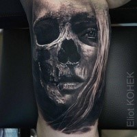 Fantastic painted biceps tattoo of woman face combined with skull