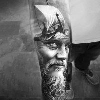 Fantastic very realistic looking viking with ship tattoo on sleeve