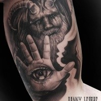 Fantasy style colored biceps tattoo of devil with human eye on hand