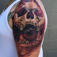 Fantasy style creepy looking shoulder tattoo of human skull stylized with eye