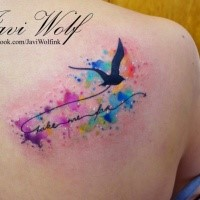 Flying black bird with lettering and colored paint drips in watercolor style shoulder blade tattoo by Javi Wolf