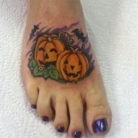 Funny Halloween pumpkins and flying bats colored tattoo on foot