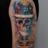 Funny smiling skeleton with monarchy crown colored tattoo on shoulder with watercolor elements