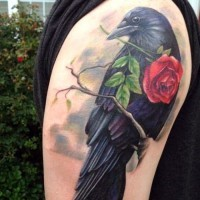 Gorgeous black crown with red rose in beak super realistic shoulder length tattoo