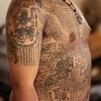 Gorgeous black ink detailed whole body tattoo of various tribal paintings and lettering