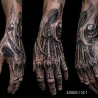 Gorgeous looking black ink detailed wrist and hand tattoo of alien like skeleton