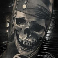 gray washed style detailed arm tattoo of pirate skull with bandage