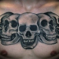 Gray washed style detailed chest tattoo of various skulls