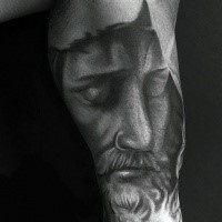 Gray washed style detailed Jesus portrait tattoo on biceps