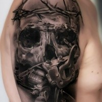 Gray washed style detailed shoulder tattoo of human skull with vine